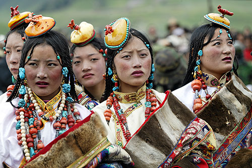 MR 1140-D6525. High in the mountains of eastern Tibet, five elaborately dressed young nomad women, their dresses lined in fur (chubas), attend the festival of Mani Gengok in 2004. This is the first time this festival has been held in ten years and the wom