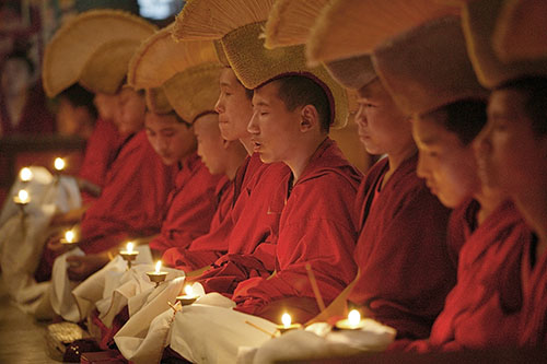 MR 1093. At the end of a long ceremony at the Tibetan monastery of Shechen in Nepal, the lamas perform an offering of butter-lamps. Each person holds a lighted lamp, and is linked to his neighbors with white scarves which, knotted together, run through th